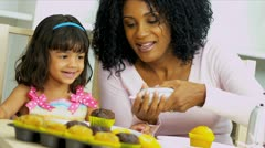 Stock Video Footage of Pretty Mother Young Child Icing Cupcakes