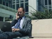 Businessman with mobile phone and laptop in the city NTSC Stock Footage