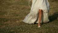 Bride running across the field Stock Footage