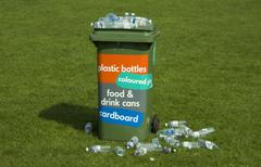 Stock Photo of picture of a recycling bin overflowing onto the grass