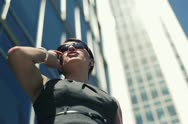 Businesswoman by the skyscrapers talking on cellphone NTSC Stock Footage