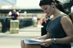 Businesswoman reading magazine during break in the city, steadicam shot NTSC Stock Footage