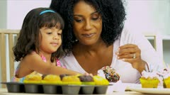 Cute Little Ethnic Girl Icing Tiny Cakes Stock Footage
