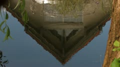 House reflecting in the soft microwaves of a small river Stock Footage