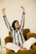 Young woman sitting with arms raised Stock Photos
