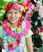 Young girl in flower necklaces and headdress Stock Photos