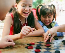 Sisters playing checkers - stock photo