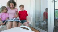 Woman reads book with two her kids at balcony on ship Stock Footage