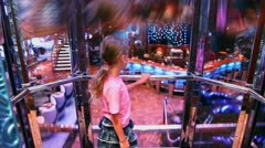 Little girl stands in elevator which lifts from restaurant Stock Footage