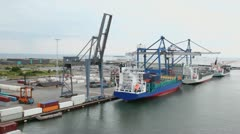 Shipment of cargo in containers to barges by huge cranes Stock Footage