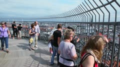 Several tourists watch cityscape from survey area near church Stock Footage