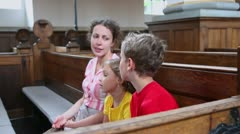 Mother with two her kids sit at bench in church Stock Footage