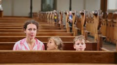 Mother with two her kids sit at bench in cathedral Stock Footage
