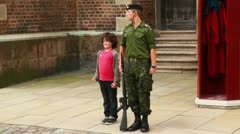 Little boy repeats movement of soldier with rifle on guard Stock Footage