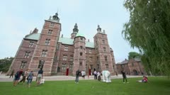 People walk and sit on grass near royal residence Rosenborg Slot Stock Footage