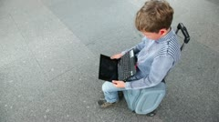 Little boy hold netbook when sits on travelling bag Stock Footage