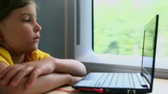 Little girl watch on notebook when sits at train near window Stock Footage