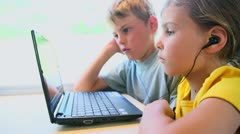 Two kids watch on netbook when sits at train near window Stock Footage