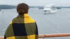 Woman wrapped in plaid stand at deck and watches on cruiser Stock Footage