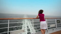 Woman stands on deck near fence and admire seascape Stock Footage