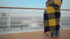 Kids wrapped in plaid stand on deck and admire seascape Stock Footage