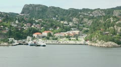 Few vessels on moorage at coastal town among forest on mountains Stock Footage