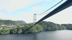 Huge pendant bridge at coast with houses among forest - stock footage