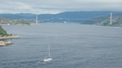 Yacht sail in bay with huge pendant bridge and town at coast Stock Footage