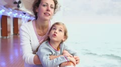 Mother with daughter stand on deck near fence and watch seascape Stock Footage