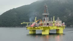 Oil rig located in sea near coastline with forest on mountain - stock footage