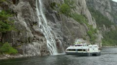 Tourists on deck of ship which stand near rock with waterfall - stock footage