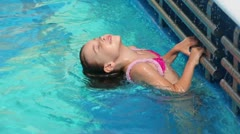 Little girl holds by tube at pool edge and plunges in water - stock footage