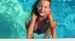 Little girl hold by pool edge and swim in pool with smile Stock Footage