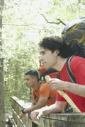 Two young men leaning on a forest railing Stock Photos