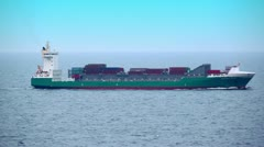Barge floats in ocean with many containers on deck Stock Footage