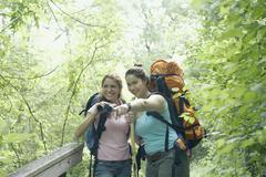 Nuoret naiset vaellus yhdessä metsässä Kuvituskuvat