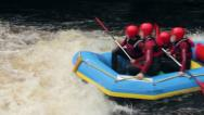 Raft paddling downriver, hitting wave on white water Stock Footage