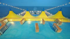 Deckchairs near pool and tents on deck of ship Stock Footage