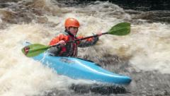 Man in kayak paddling on stopper wave Stock Footage