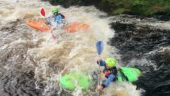 Two men in kayaks paddle down river into white water Stock Footage