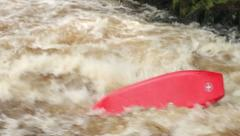 Man in kayak paddles down river into white water and capsizes Stock Footage