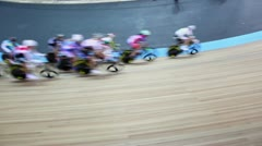 Bicyclists ride by track turn during race in stadium Stock Footage