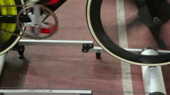 Cyclist spins pedals on bike at one place in rollers frame - stock footage