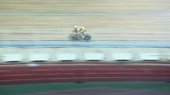 Bicyclist rides by track during race in gymnasium Stock Footage