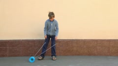 Little boy holds two sticks and plays toy near wall Stock Footage