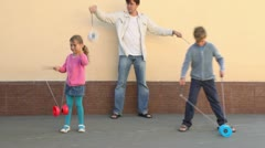 Father and children boy and little girl play toy near wall Stock Footage