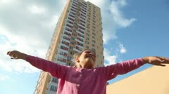 Little girls spins with arms up sideward near dwelling house - stock footage
