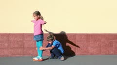 Boy rotates girl which spins with arms up sideward near wall - stock footage