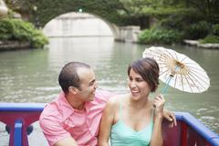 Couple sitting in a boat with parasol Stock Photos