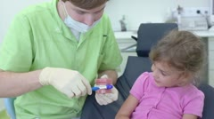 Dentist shows for little girl how to clean teeth by brush Stock Footage